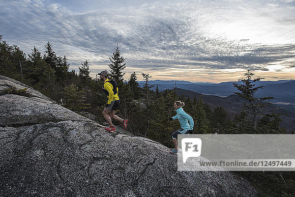 Trail runners heading up the steep and open granite slabs near the summit of Black Cap mt.