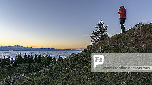 someone with red coat and black pants photographing the sunrise over the sea of clouds on the Geneva Lake with the Alpine chain in the background  in the Vaud Canton  Switzerland