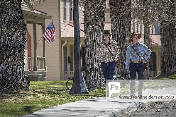 Two young women stroll down Officer's Row in Mammoth Hot Springs  Yellowstone.