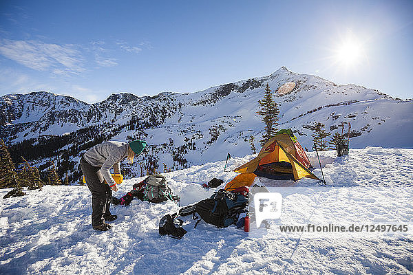 A young woman begins to pack her bag after camping overnight in the Coast Mountains  British Columbia  Canada.