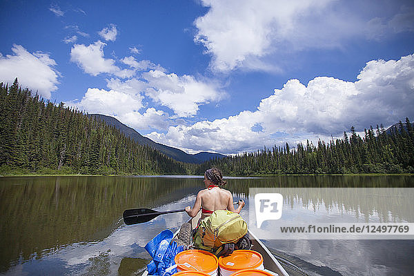 A woman paddles a canoe over Indianpoint Lake during a canoe trip in Bowron Lake Provincial Park.