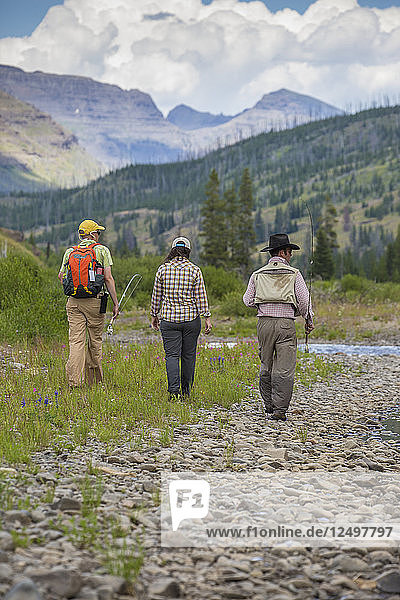 Two Men And A Woman Walking Along The Mountain River Just North Of Yellowstone National Park