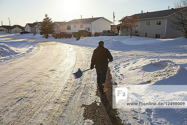 An man walks a suburban street with a snow shovel in his hand with intentions to shovel snow off his neighbour's driveway.