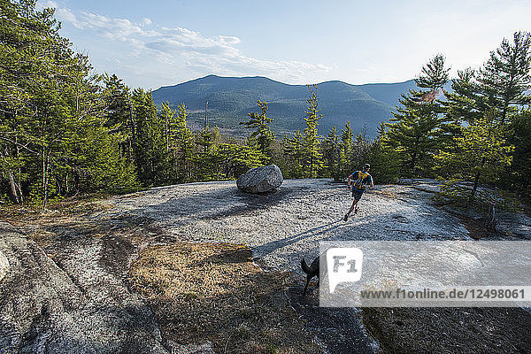 Man and dog running over the granite slabs near the summit of Whitehorse ledge overlooking the Moat mountains.