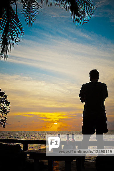 Silhouette Of A Man Watching The Sunset From A Beach On Koh Chang Island  Thailand