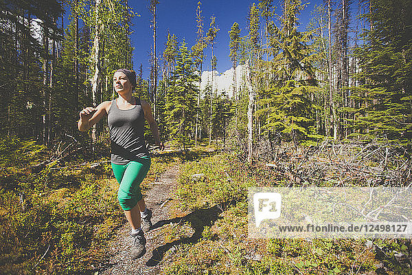 An active woman woman trail running in Bowron Lake Provincial Park.