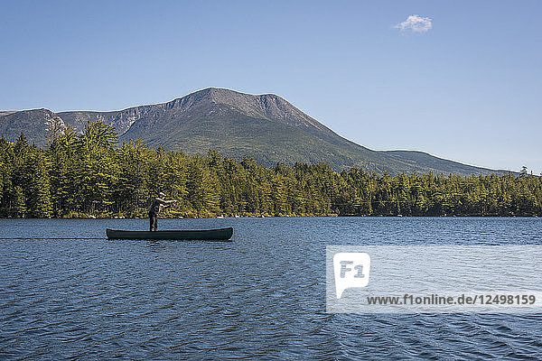 Fisherman casting in Kidney Pond with Mount Katahdin in the background.