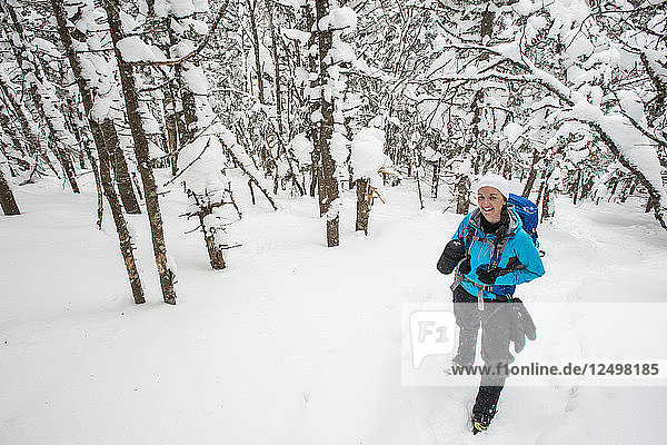 Woman Hiking In The Snow Covered Forests Of New Hampshire