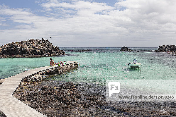 Family relaxing on a wooden jetty in Lobos Island (Fuerteventura) with a boat and clear calm blue ocean
