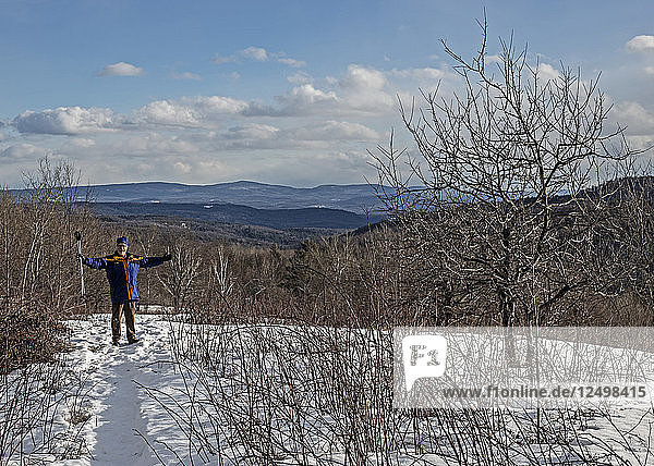 A man celebrates hiking to an overlook in the snow.