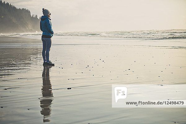 A young woman is reflected on the sand at Neskowin Beach  Oregon.