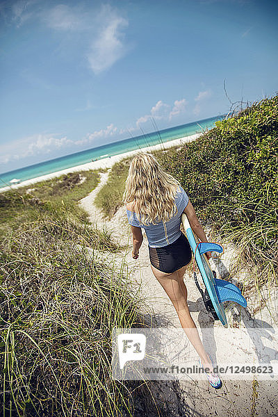 A young woman walks with a surfboard along a path to the beach.