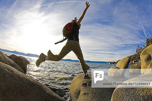 Woman Jumping On Rock In Lake Tahoe