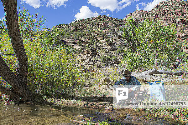 Filtering water on a creek in Desolation Canyon along the Green River  Utah.
