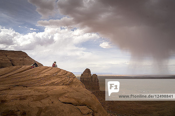 A woman sits on a cliff in the desert with a storm in the distance