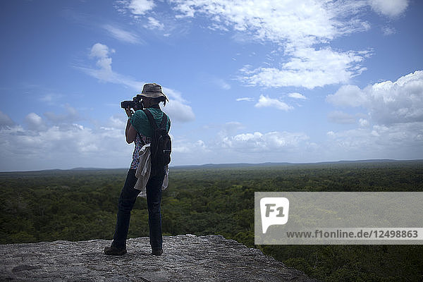 A photographer takes pictures of the jungle of top of a temple in the Mayan city of Calakmul  in Calakmul Biosphere Reserve  Campeche state  Yucatan Peninsula  Mexico