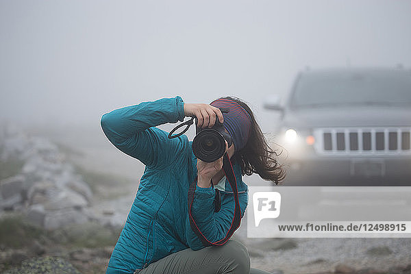 Female Photographer Taking Picture On Mount Washington During Heavy Cloud Coverage