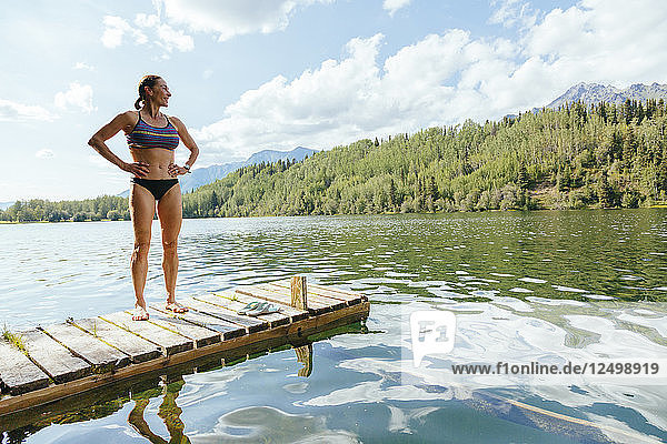 A Woman Is Standing On A Jetty After A Swim In Long Lake Along The Mccarthy Road  Alaska  Usa