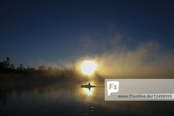 A kayaker enjoys the sunrise as steam rises from Lake Pleasant in Conover  Wisconsin on a brisk fall morning.
