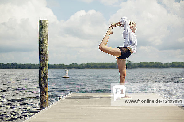 A young woman does yoga on a pier overlooking a lake in Panama City Beach Florida.