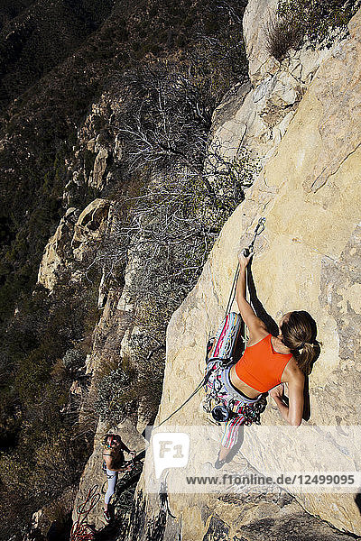 A woman wearing a red tank top and striped pants climbs The Rapture (5.8) on Lower Gibraltar Rock in Santa Barbara  California. The Rapture is a very nice and unbelievably well protected route on the left ar?™te of Lower Gibraltar Rock.