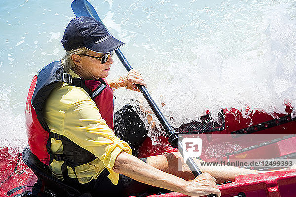Woman in a kayak with a wave crashing over the boat