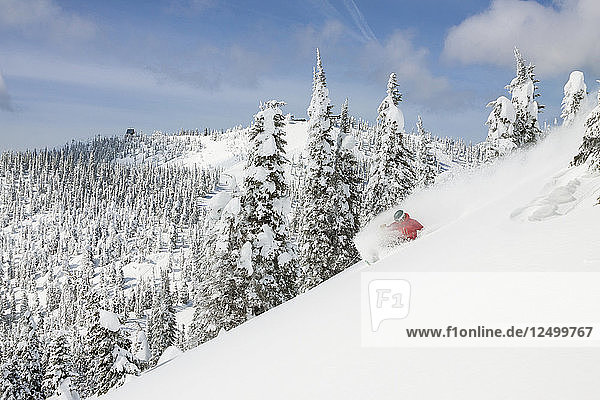 Male Skier Makes A Deep Powder Turn On Snowy Landscape In Whitefish  Montana  Usa