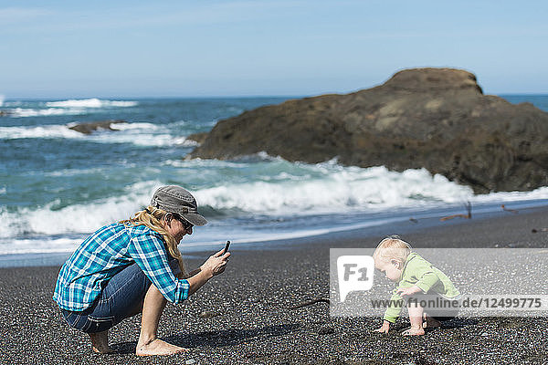 Mother taking smartphone photo of her young daughter playing on the beach. California Coast