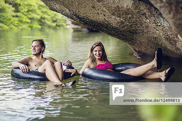 A young man and woman smile while tubing down a river underneath a rock overhang.