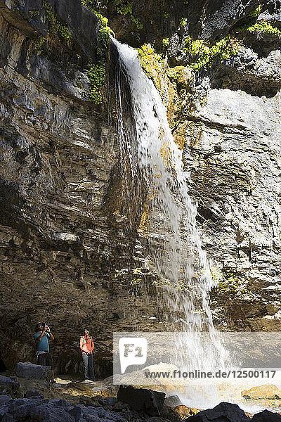 Couple Under Spouting Rock Waterfall At Hanging Lake Trail  Colorado