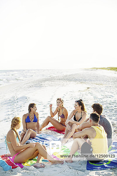 Group Of Friends Sitting And Enjoying Together On Beach