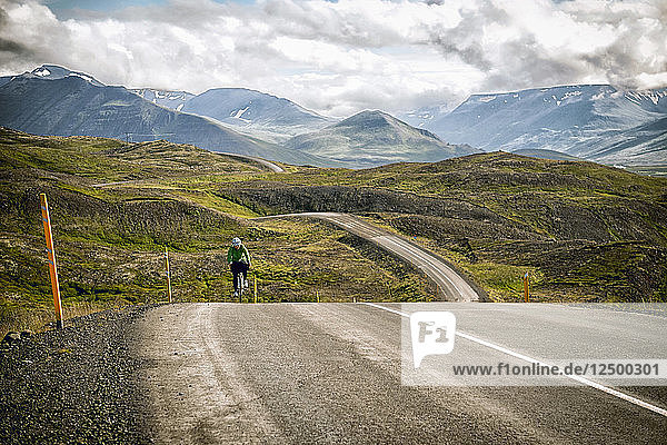 A Woman Cyclist Crests A Hill In The Mountains Of North Iceland