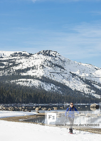 Woman skiing along shores of Donner Lake