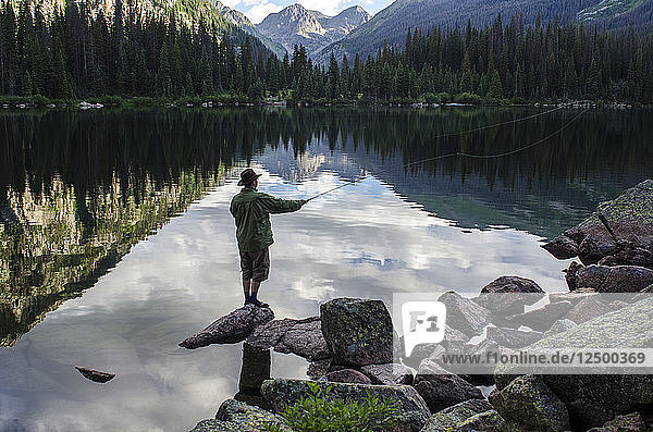 Photographer Jeremy Wade Shockley casts his fly line accross Emerald Lake  Weminuche Wilderness  Southwest Colorado.