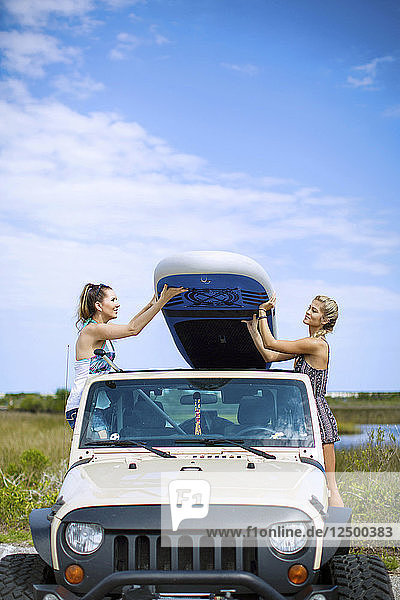 Two Friends Carrying Paddleboard Together Placing It On Off Road Vehicle