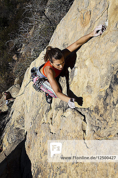 A woman wearing a red tank top and striped pants climbs The Rapture (5.8) on Lower Gibraltar Rock in Santa Barbara  California on. The Rapture is a very nice and unbelievably well protected route on the left ar?™te of Lower Gibraltar Rock.