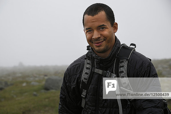Portrait Of Smiling Male Photographer On Mount Washington During Heavy Cloud Coverage