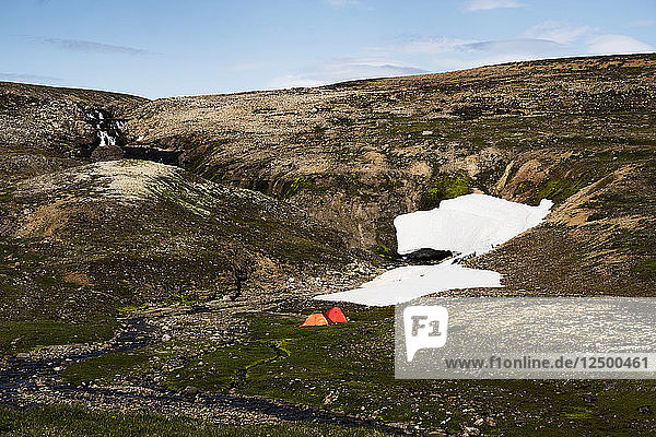 Distant View Of Two Tents Beneath Snowfields And Waterfalls In Iceland