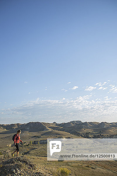 An adult woman day hiking and enjoying the views in Theodore Roosevelt National Park in North Dakota.