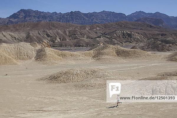 Woman Running Through The Desert Area Of Death Valley National Park  California  Usa