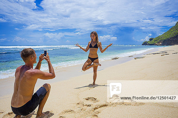 Young man making a photo of pretty woman on a beach.
