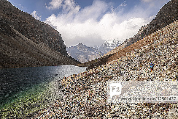 Male Trail Runner Enjoys Some Smooth Single Track Along The Clear Waters Of High Alpine Lake In Bhutan