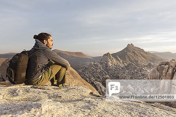 A Young Man Relaxing On Rock Exploring Desert Landscape