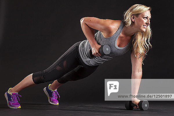 Woman in plank position doing upright row hand weight lifting