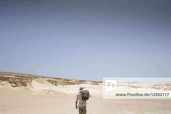 Man with backpack standing in desert