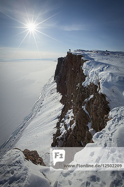 Long Exposure Of Person Standing On Snowy Cliff In Arctic Bay