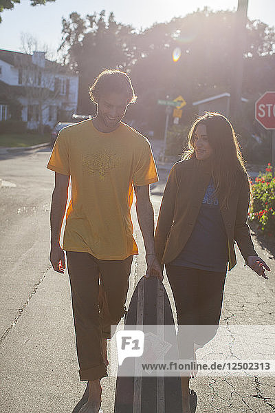 A young man and woman walking a San Diego neighborhood. California.