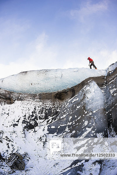 Climber on the icelandic glacier Solheimajokull during winter. South Iceland.