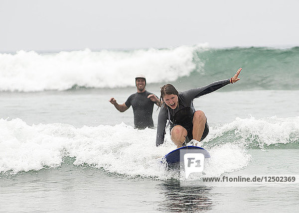 A woman catches an inside wave as her boyfriend cheers her on at San Onofre State Beach in San Clemente  Calif.  on July 26  2014.