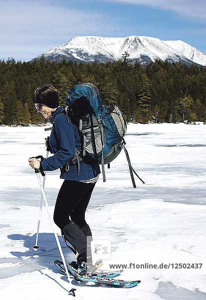 A women seen in the forground crossing Lost Pond  a frozen pond in Baxter State Park. In the Background can be seen Mount Katadin